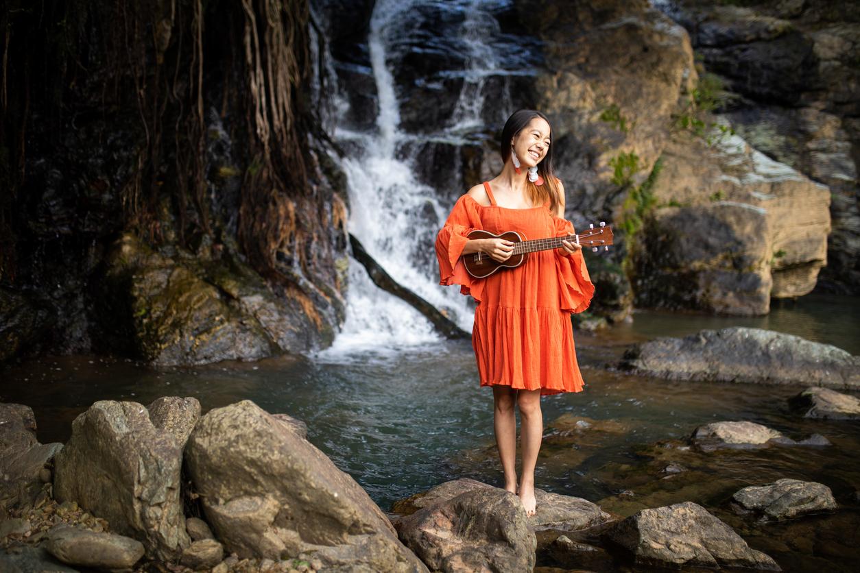 滝を背景にウクレレを弾く女性