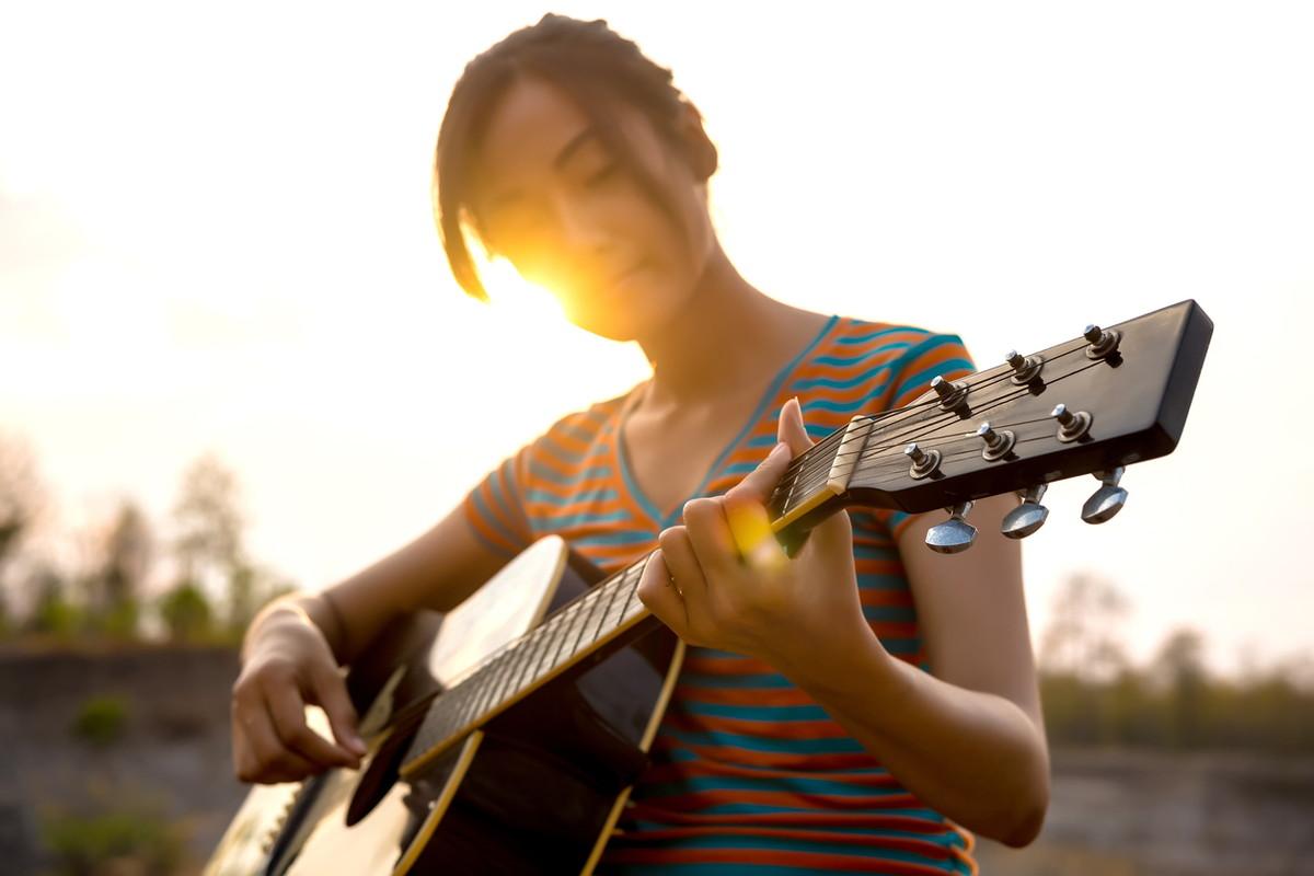 夕日バックにギターを弾く女性
